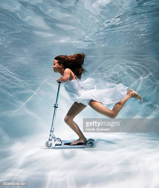 Girl (12-13) riding scooter underwater, side view