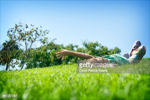 Girl Rolling In Grass Down A Hill