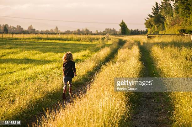 Girl running along path in field