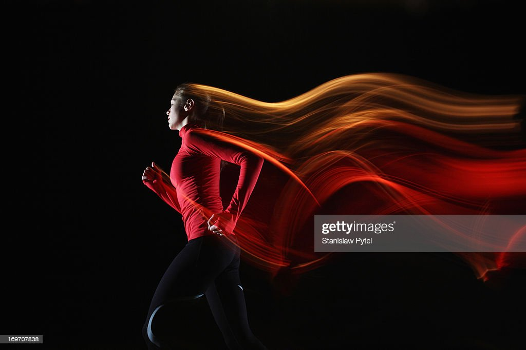 Girl running and leaving light streaks : Stock Photo