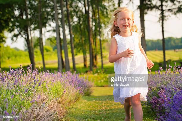 Y sonriente niña corriendo en el campo de lavanda en sunset