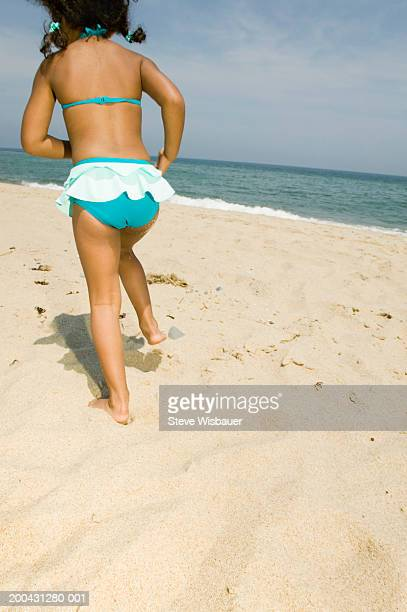 Girl (4-6) running at beach, rear view