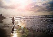 Girl running at beach sunrise