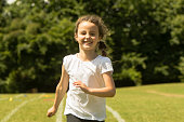 Young child sprinting hard and happily during summer traditional school event
