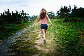 Girl running away in a rural setting