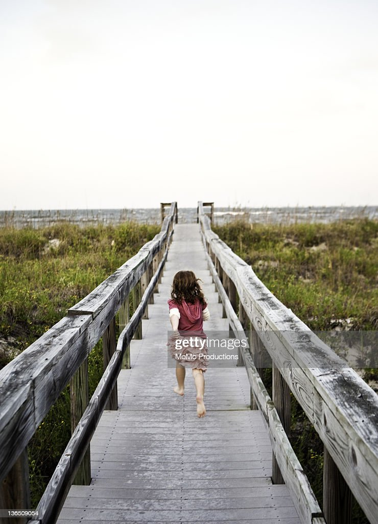Girl running down boardwalk at beach : Stock Photo