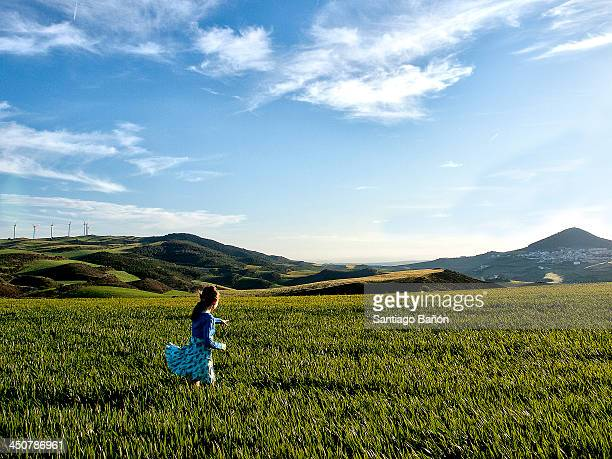 Girl running in a wheat field in spring