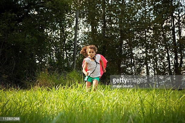 Menina a correr em campo com uma capa
