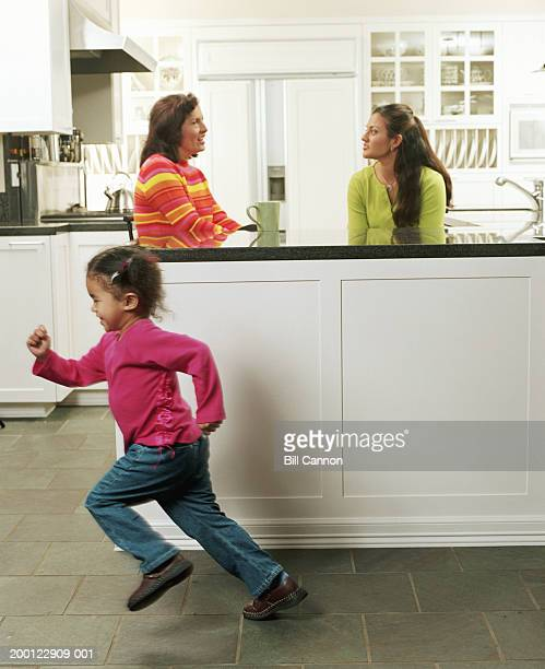 Girl (2-4) running in kitchen, mother and grandmother in background