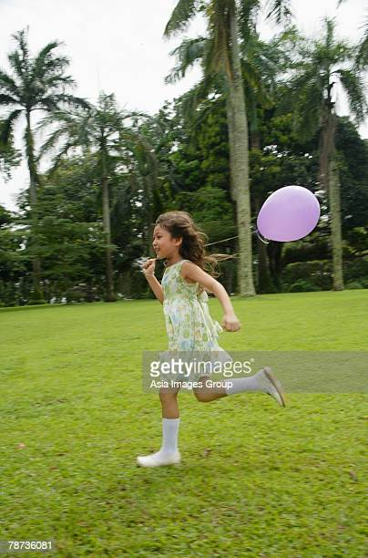 Girl running in park, purple balloon flying behind her