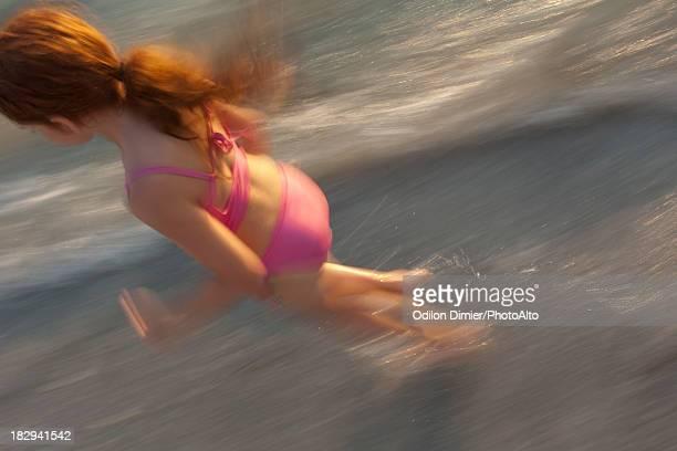 Girl running in surf at beach, blur