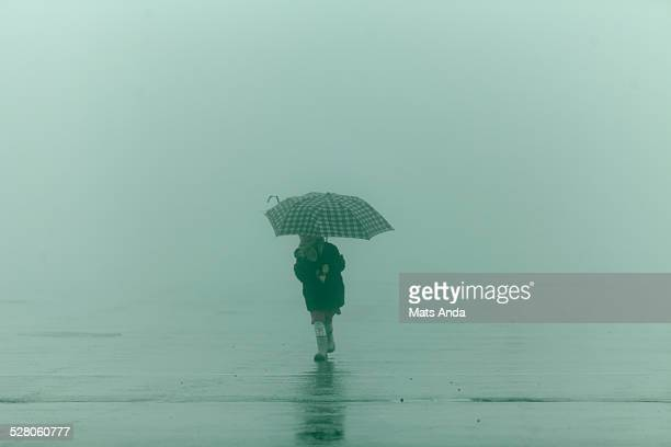 Girl running in the fog with umbrella