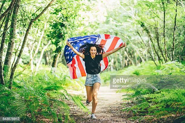 Ragazza corre nella foresta con una bandiera americana
