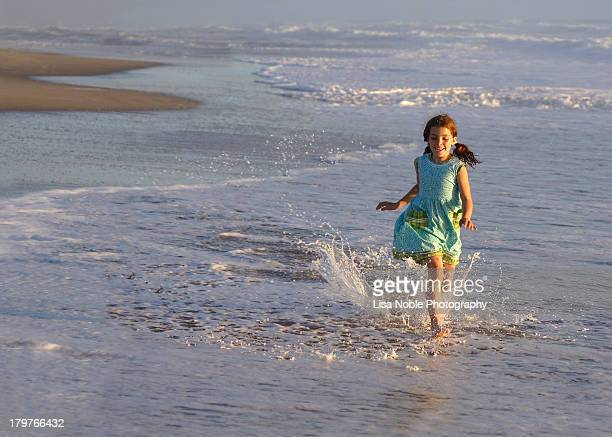 Girl running in water at beach at sunset