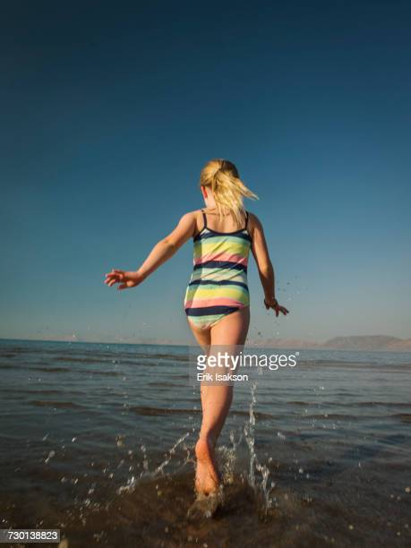 Girl (4-5) running into lake
