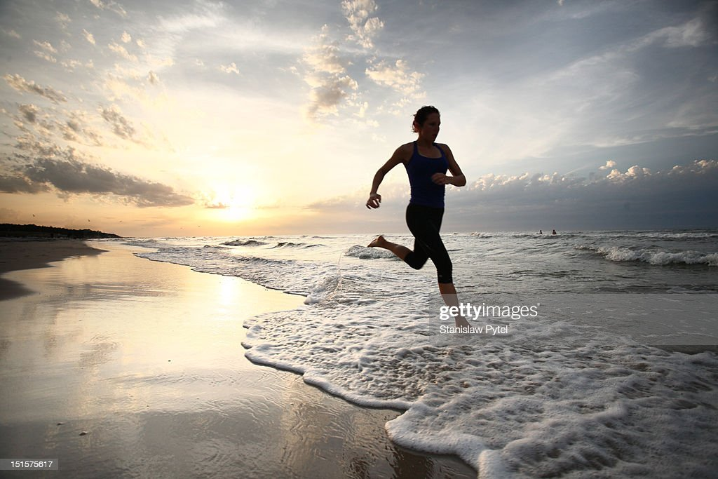 Girl running on beach with sunset at back : Stock Photo