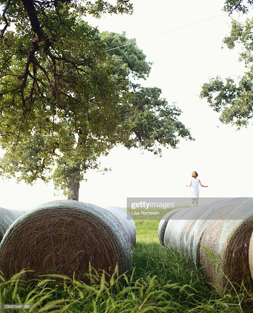 Girl (5-7) running on hay bales, rear view : Stock Photo