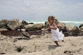 Girl (4-5) running on sea shore