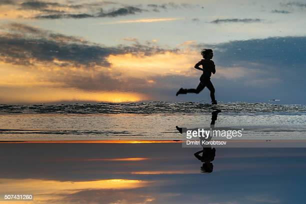 Girl running on the Stroomi beach in Tallinn during the sunset