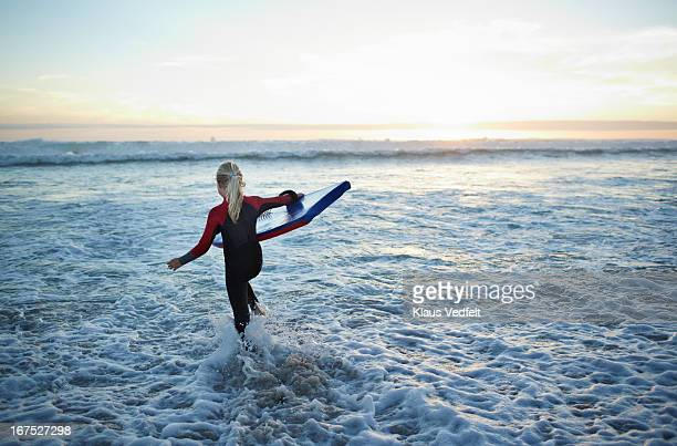 Girl running out in the ocean with bodyboard