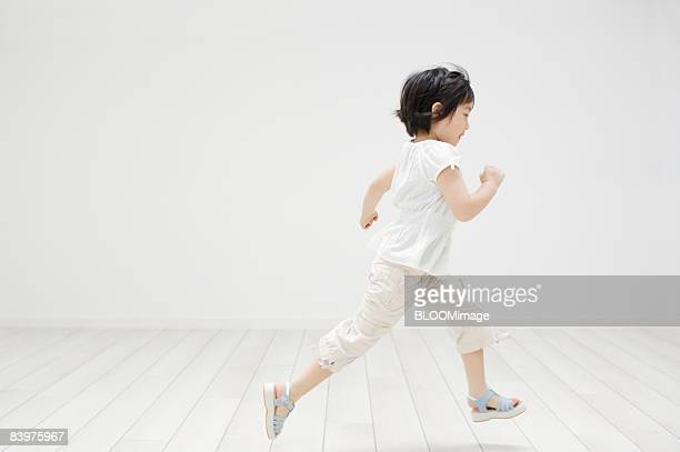 Girl running, side view, indoors