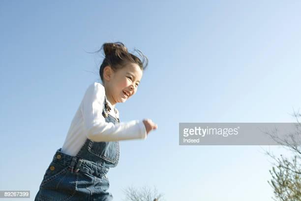 Girl (8-9) running, smiling
