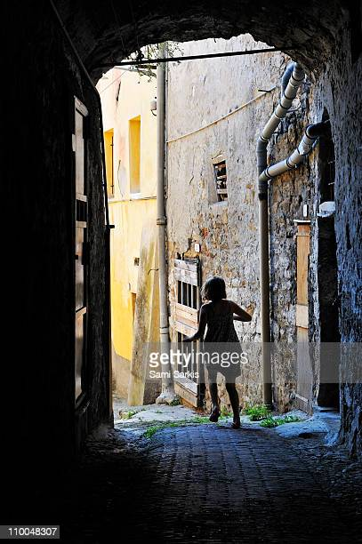 Girl running through a cobblestone street, Italy