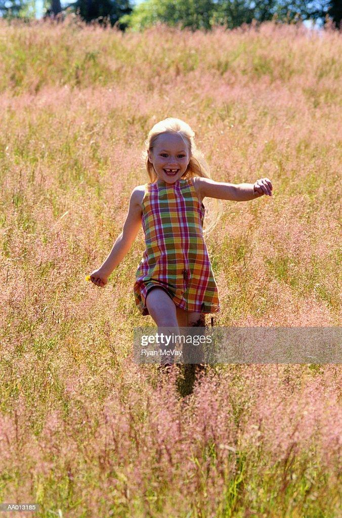 Girl Running Through a Meadow : Stock Photo