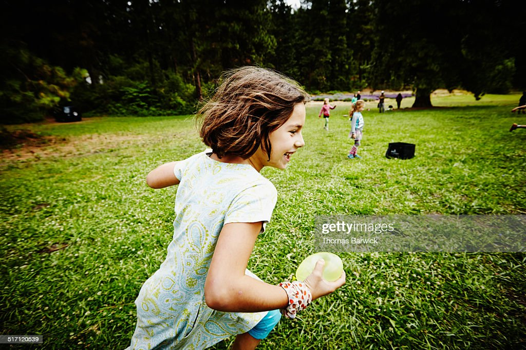 Girl running through field with water balloon