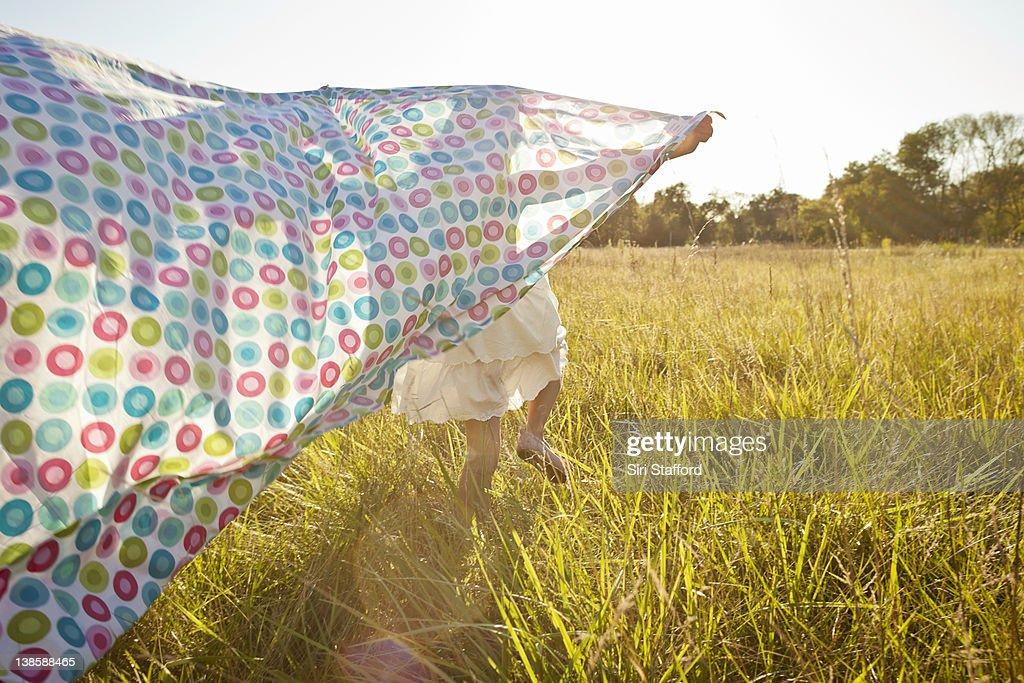 Girl running through grass with sheet behind her : Stock Photo