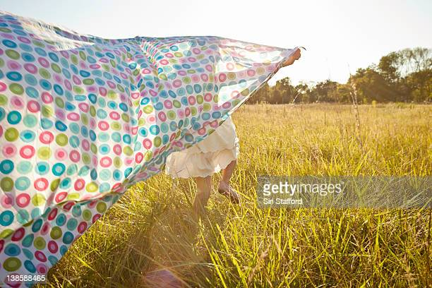 Girl running through grass with sheet behind her
