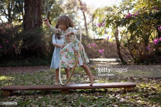 Girl running through plastic hoop in garden