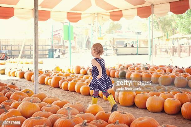 Girl running through pumpkins