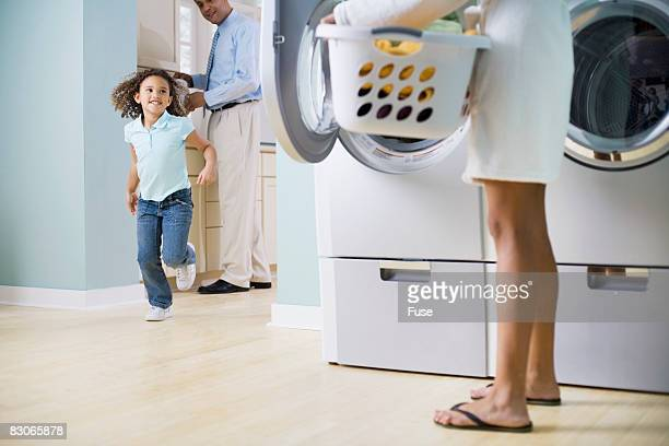 Girl Running To Mother in Laundry Room