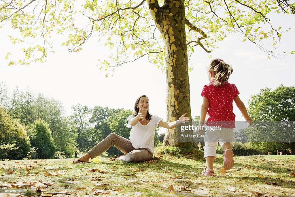 Girl running to mother in park : Stock Photo