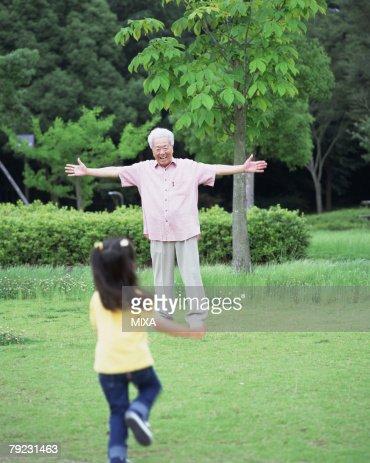 A girl running toward a grand father : Stock Photo