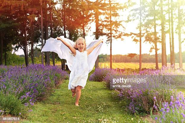 Girl running with a scarf in lavender field at sunset