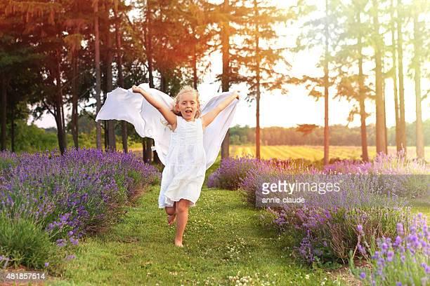 Mädchen läuft mit einem Schal in Lavendel Feld bei Sonnenuntergang