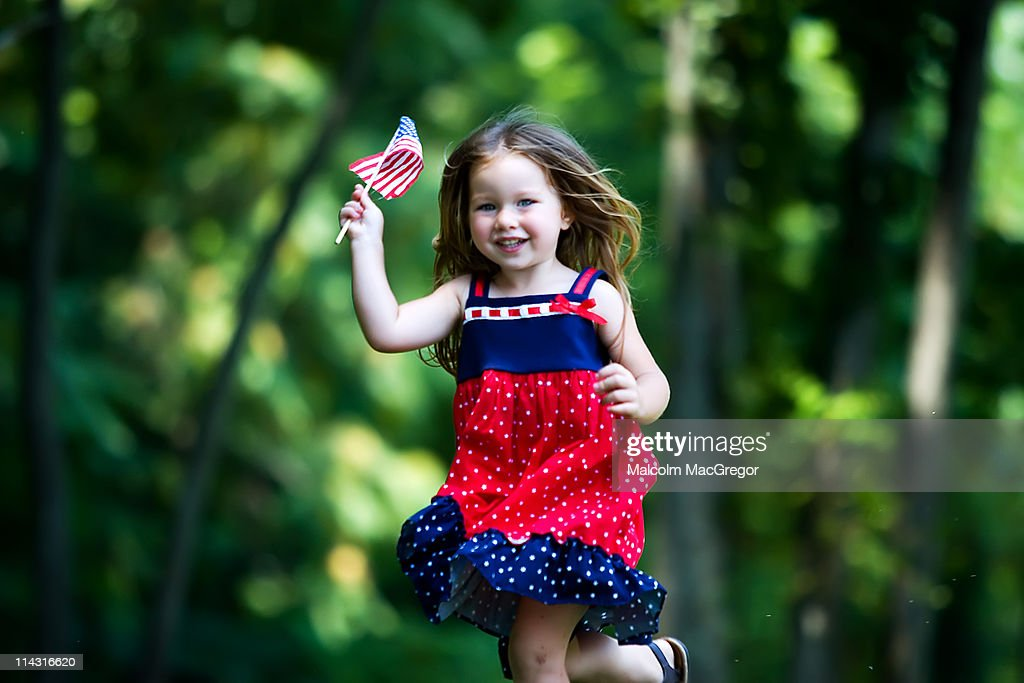 Girl running with american flag in hand