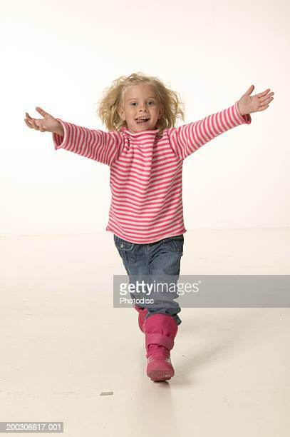 Girl (4-5) running with arms outstretched, portrait