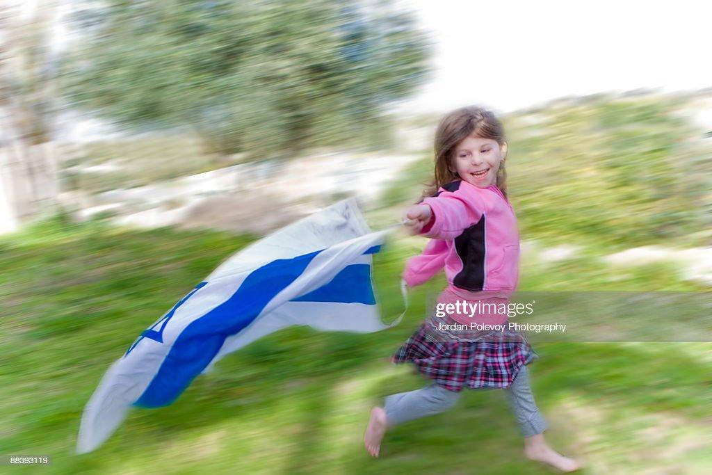 Girl running with Israeli flag