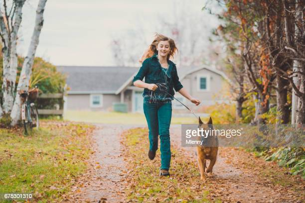 Girl running with the dog on a beautiful autumn day
