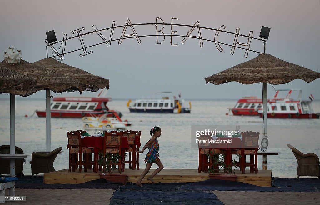 A girl runs along the sea front past the entrance to a private beach retreat at dusk in Naama Bay on May 30, 2011 in Sharm El Sheikh, Egypt. Protests in January and February brought an end to 30 years of autocratic rule by President Hosni Mubarak who will now face trial. Food prices have doubled and youth unemployment stands at 30%. Tourism has yet to return to pre-uprising levels.