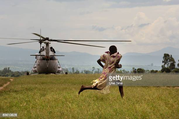 A girl runs as a UN helicopter lands at a refugee camp on November 07 2008 in Kiwanja Democratic Republic of Congo Over 250000 people have been...
