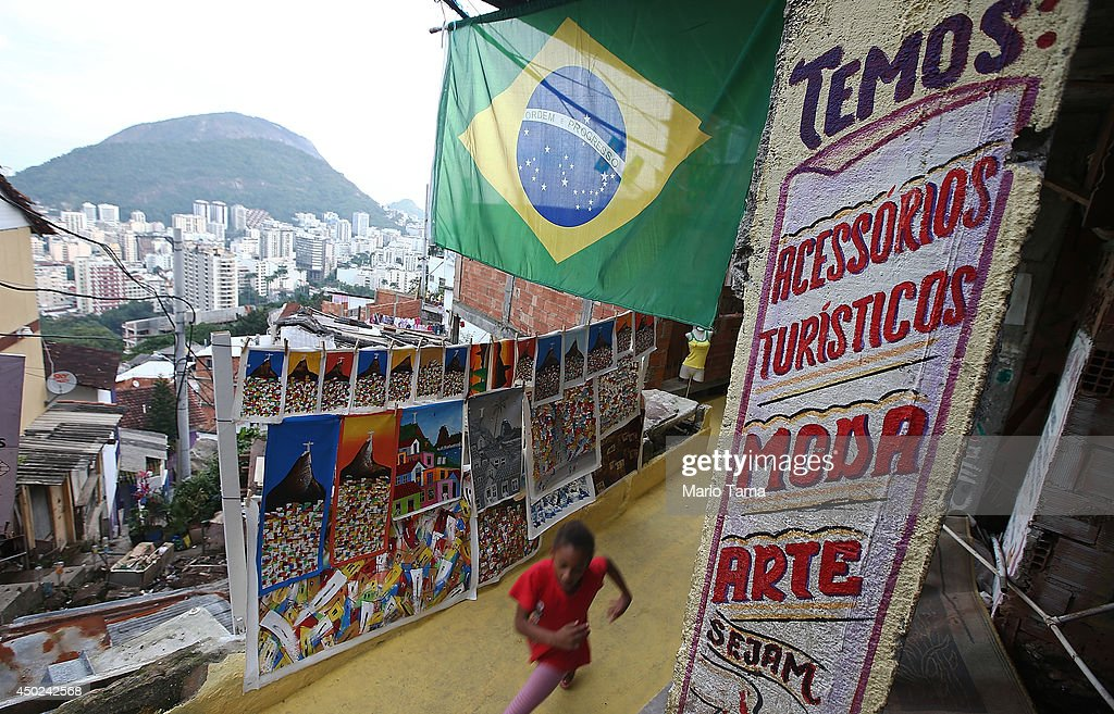 A girl runs beneath the Brazilian flag in the Santa Marta shantytown, or 'favela', on June 7, 2014 in Rio de Janeiro, Brazil. Brazil is in final preparations to host the 2014 FIFA World Cup which kicks off June 12.