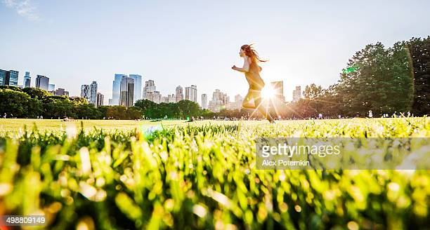 Girl runs in front of Manhattan skyline in Central Park