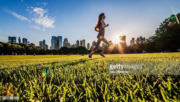 Girl runs in front of Manhattan skyline in Central Park