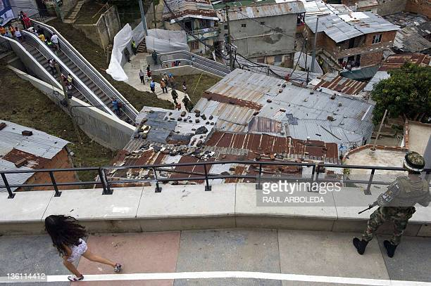 A girl runs next to a Colombian soldier during the inauguration of the escalators at Comuna 13 neighborhood in Medellin Antioquia department Colombia...