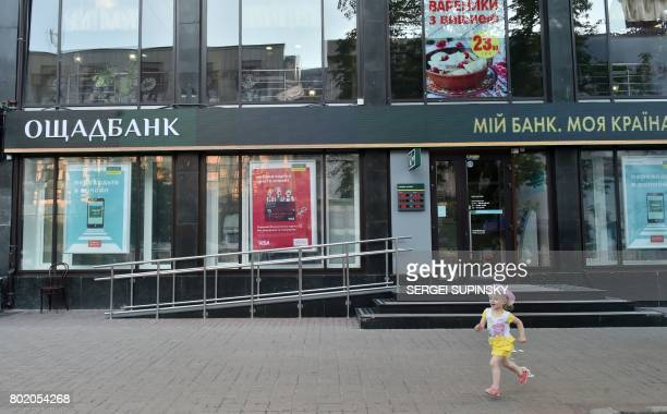 A girl runs past a closed branch of Oschadbank on June 27 2017 in Kiev Wave of cyberattacks that began in Russia and Ukraine on June 27 was wreaking...