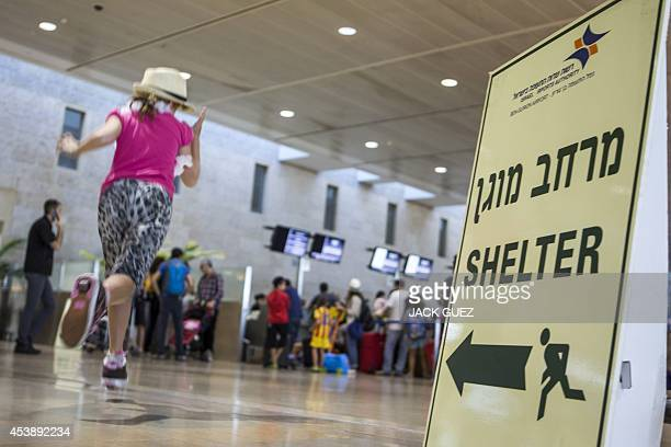 A girl runs past a sign directing passengers to a shelter at Ben Gurion International airport near the Mediterranean Israeli coastal city of Tel Aviv...